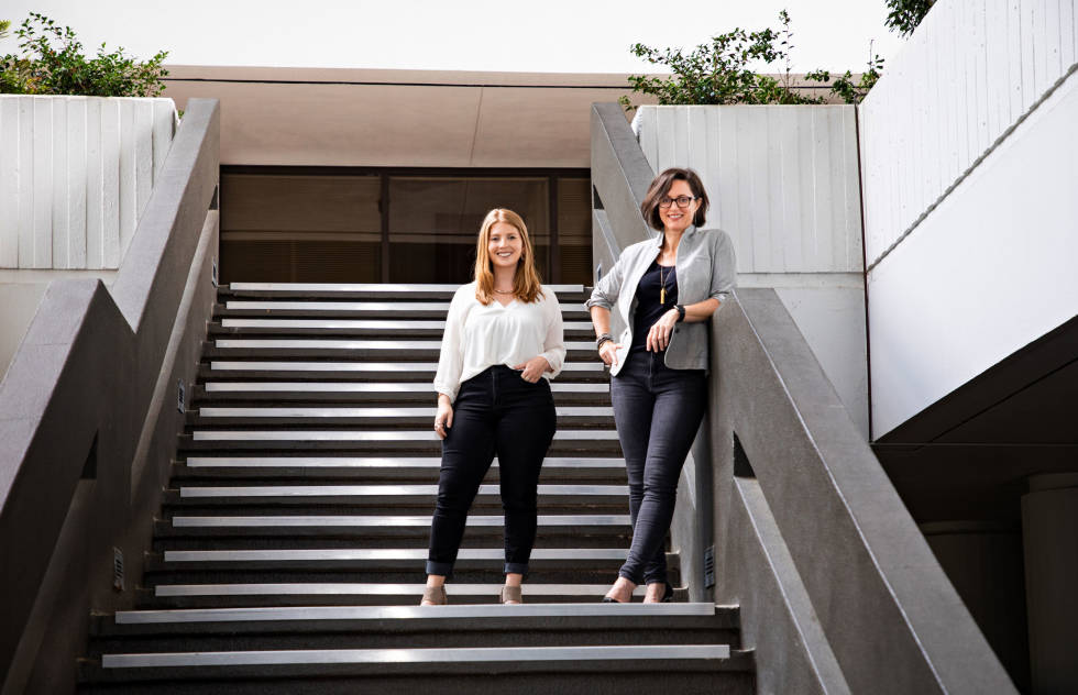 Mary Frances and Jamie of the Roadie team standing together on steps outside. Both women are smiling and looking downward at the photographer.