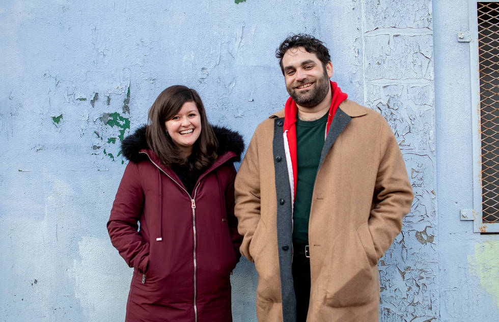 Ric and Morgan from the Adhoc Presents team stand smiling against a light blue wall.