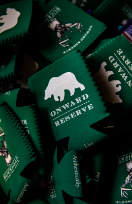 Pile of dark green drink koozies that say Onward Reserve and have their white bear silhouette logo.