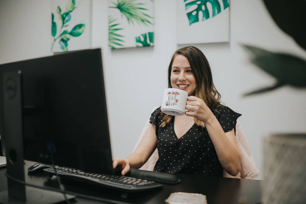 Image of person at their desk holding a mug