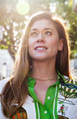 Portrait of Katie Fritts, owner of Underclub. She is outside and looking up. The sun is shining behind her.