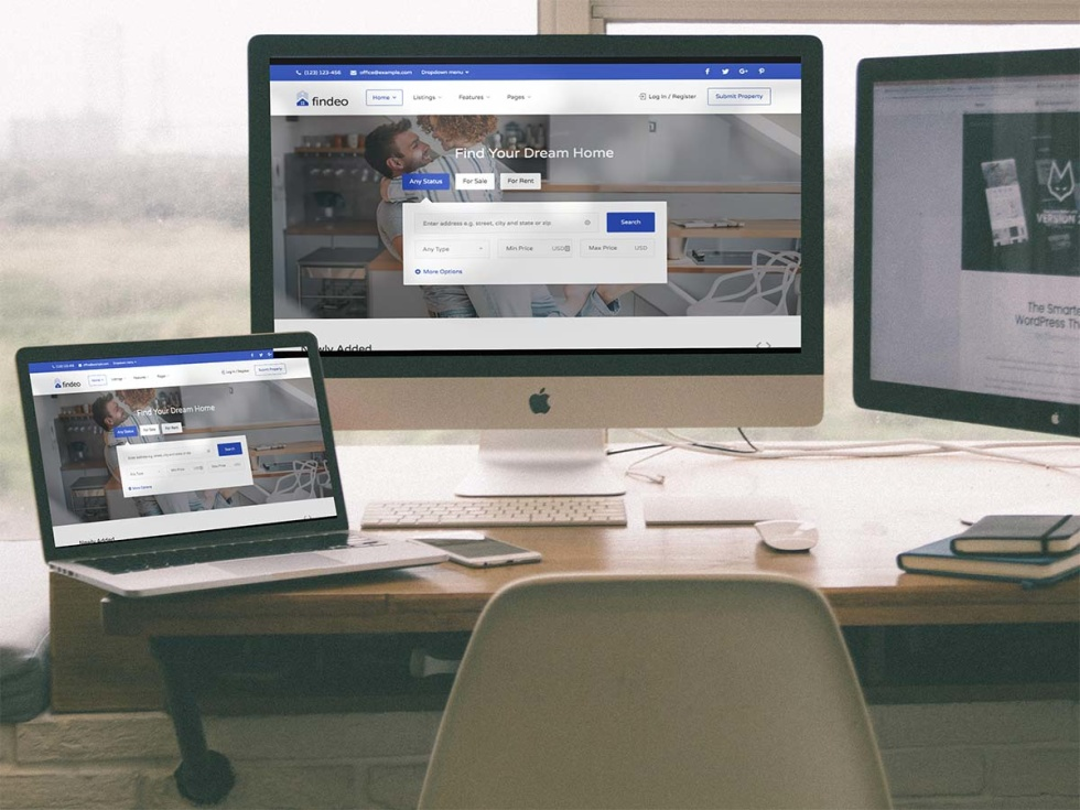 Photo of empty desk that has two desktop computers and a laptop. Each desktop displays a different version of the same website.