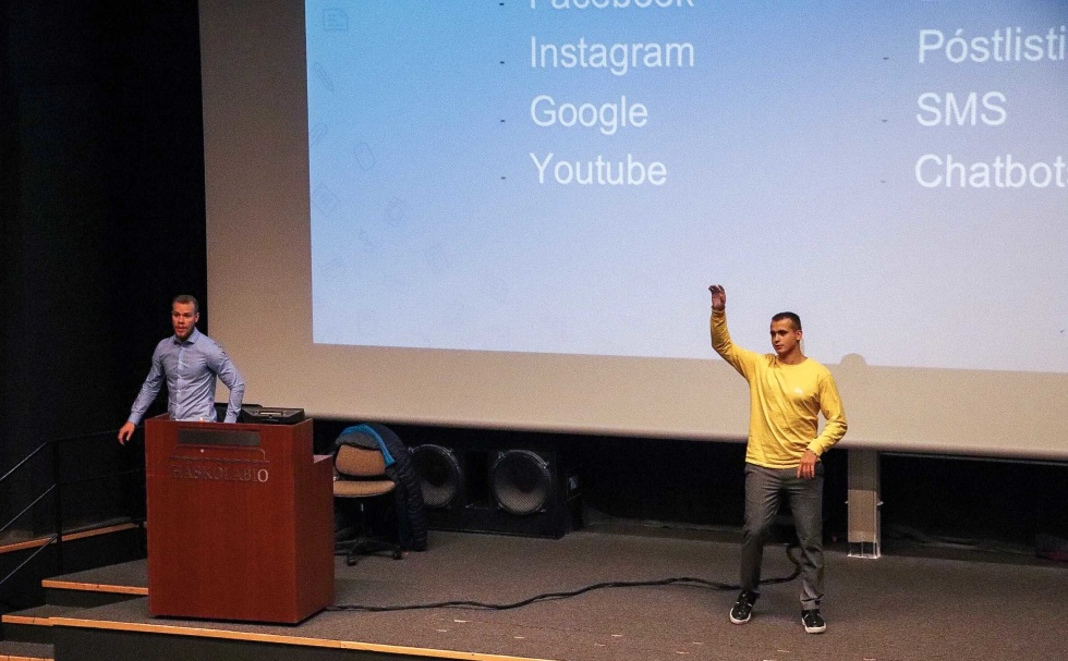 Photo of two men on stage giving a presentation.
