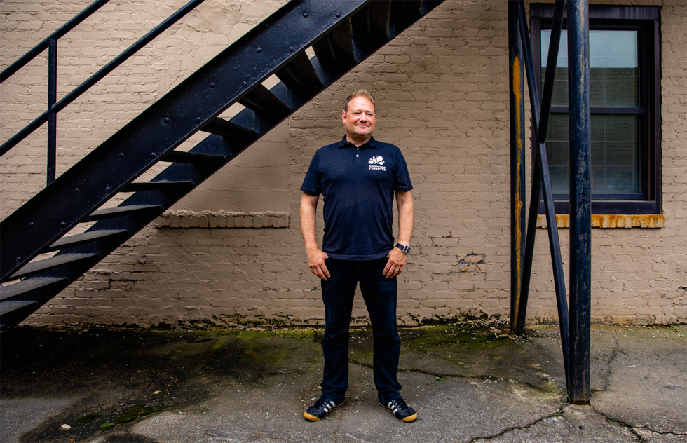 Freshtix Co-founder Iain Bluett standing and smiling outside of the Freshtix office.