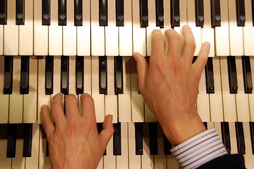 photo of hands playing organ