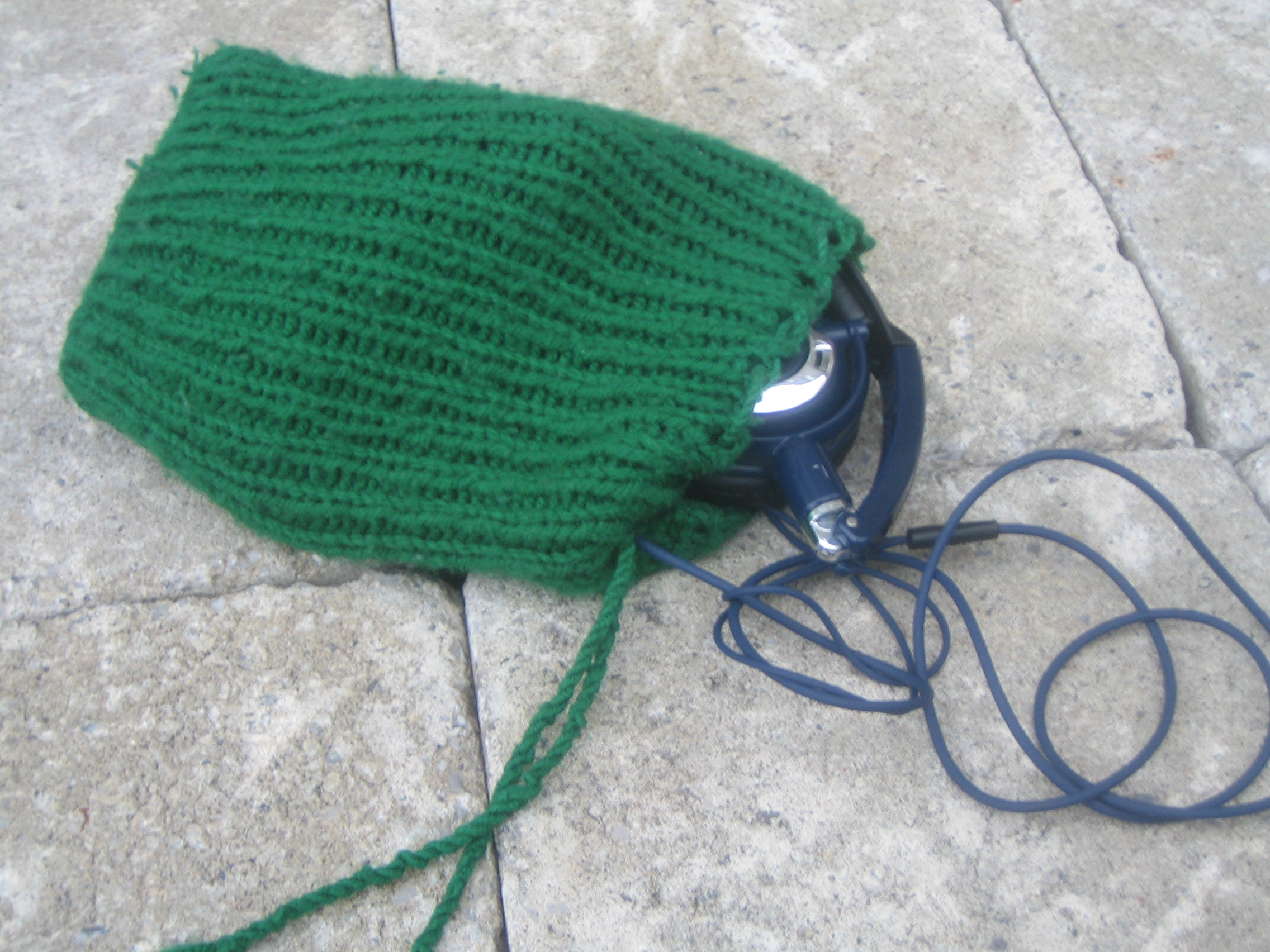 A small green bag done in 1 by 1 ribbing, with a twisted cord drawstring and a pair of headphones partially out.