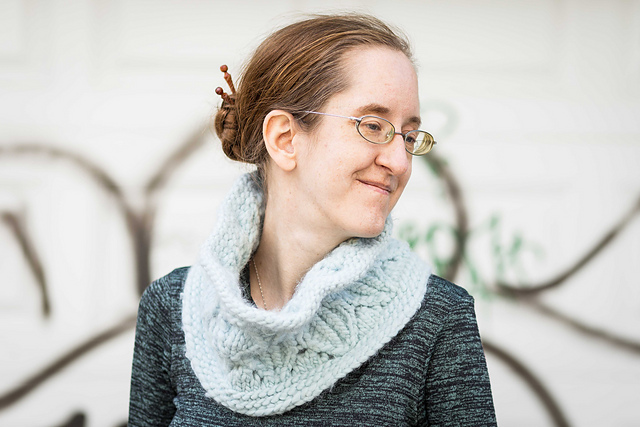 A woman wearing a blue bulky knit cowl. T