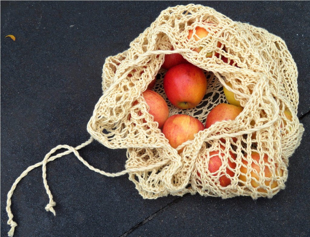 A drawstring bag mesh bag left partially open. The bag has apples inside